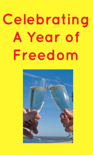 Celebrating a year of freedom in red text on a yellow background with a picc of two champagne glasses being clinked together
